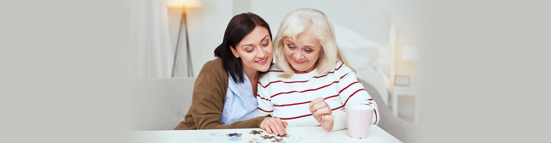 elder woman with caregiver solving a puzzle concept