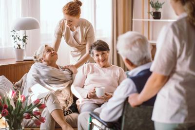 caregiver comforting elderly women in nursing home