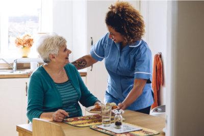caregiver serving elder woman a meal concept