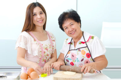 elder woman assisted by caregiver in preparing a meal