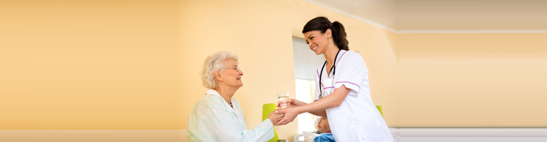 caregiver offering elder woman a glass of water concept