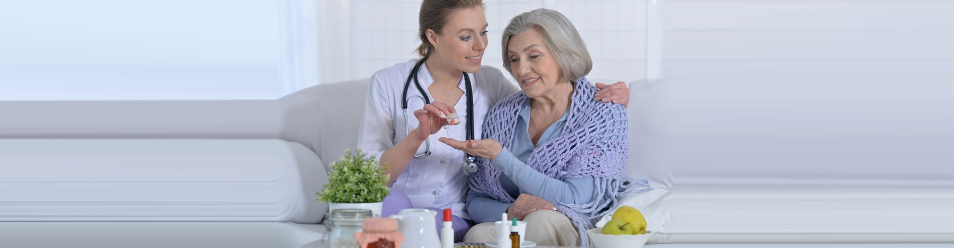 caregiver giving elder woman a medicine concept