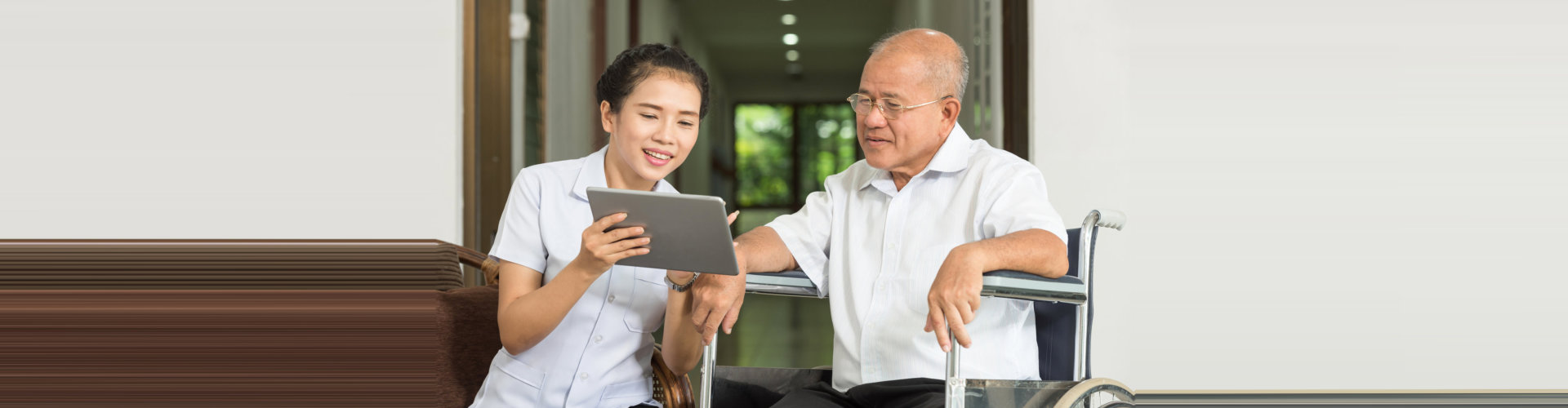 caregiver showing a photo from the tablet to an elder man concept